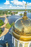 Golden cross on the main dome of the Epiphany Cathedral, Nilov Monastery, Tver region. In the background you can see the coastline of peninsula Svetlitsa and Royalty Free Stock Photo