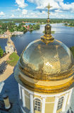 Golden cross on the main dome of the Epiphany Cathedral, Nilov Monastery, Tver region. In the background you can see the coastline of peninsula Svetlitsa and Stock Photos