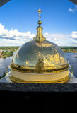 Golden cross on the main dome of the Epiphany Cathedral, Nilov Monastery, Tver region. In the background you can see the nearest shore of the lake Seliger Stock Photo
