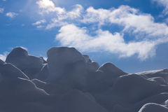 Backgrounds - Shadowed Snow with Blue Sky. Image of snow with a beautiful blue sky in the background and a small amount of sun glare to highlight the edges stock photography