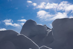Backgrounds - Shadowed Snow with Blue Sky. Image of snow formations with a nice bright blue sky in the background stock photo