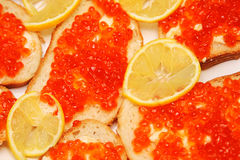 Backgrounf of bread and butter with red caviar and lemon stock photography