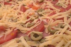 Backgroung ha fatto di formaggio grattugiato bianco, pomodori, olive Fotografia Stock