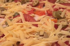 Backgroung ha fatto di formaggio grattugiato bianco, pomodori, olive Fotografia Stock Libera da Diritti