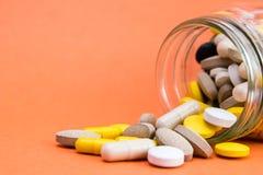 Backgrpund atómico de la mandarina Las drogas de las vitaminas dispersaron y se derramaron hacia fuera cerca de un envase de cris fotos de archivo libres de regalías