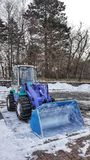 Backhoe για να ανασκάψει το χιόνι στο έδαφος Στοκ Φωτογραφίες
