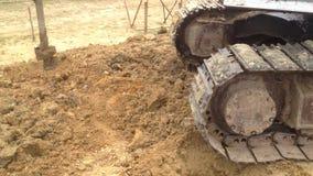 Backhoe με μια τρυπώντας με τρυπάνι συσκευή σε ένα εργοτάξιο οικοδομής απόθεμα βίντεο