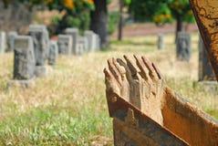 Backhoe в погосте с надгробными плитами на заднем плане Стоковая Фотография