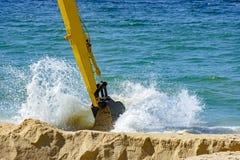 Backhoe извлекая песок из пляжа стоковые фото