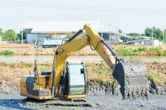 Backhoe работая в болоте грязи стоковое фото