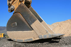 Backhoe Bucket. With a large pile of dirt in the background against a clear blue sky Stock Photos