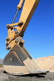 Backhoe Bucket. With a large pile of dirt in the background against a clear blue sky Stock Photography