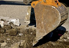 Backhoe bucket lifts up  chunks of concrete. A backhoe picks up a concrete slab in a demolition curbside project in a hydraulic bucket Stock Photo