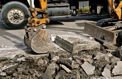 Backhoe bucket lifts up  chunks of concrete. A backhoe picks up a concrete slab in a demolition curbside project in a hydraulic bucket Stock Images