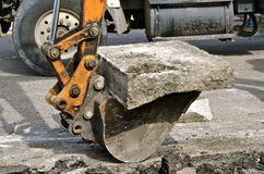 Backhoe bucket lifts up  chunks of concrete. A backhoe picks up a concrete slab in a demolition curbside project in a hydraulic bucket Royalty Free Stock Images