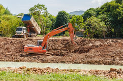 Backhoe on the construction at digging the pit Stock Photo