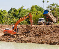 Backhoe on the construction at digging the pit. SATTAHIP , THAILAND – DECEMBER 31, 2015 : Backhoe and truck on the construction at digging the pit. Preparatory Stock Photos