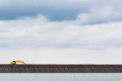 Backhoe on dam crest Royalty Free Stock Photography
