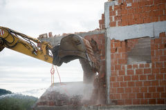 Backhoe demolishing a brick house Royalty Free Stock Images