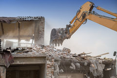 Backhoe demolishing house Stock Images
