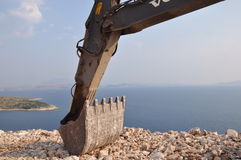 Backhoe digger by ocean. Mechanical backhoe digger arm and stones with ocean in background royalty free stock image