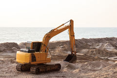Backhoe digging in the sand Royalty Free Stock Image