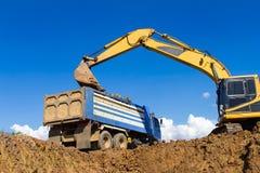 Backhoe digging and trucks. stock image