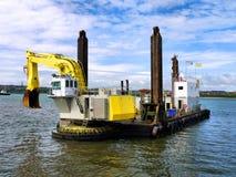 Backhoe Dredger Beginning Dredging Operations. Backhoe Dredging Barge beginning dredging operations on harbour reclamation works stock images