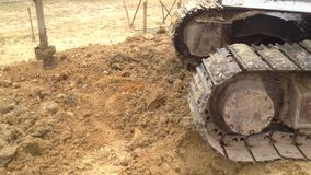 Backhoe with a drilling device at a construction site stock video