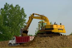 Backhoe and Dump Truck. Working on construction site Stock Images