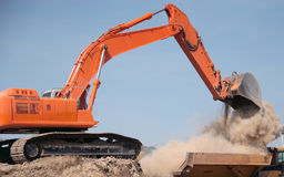 Backhoe Dumping Dirt. Backhoe construction machine dumping dirt into dump truck and stirring up dust Stock Photo