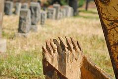 Backhoe em um cemitério pronto para escavar um outro furo Imagens de Stock Royalty Free