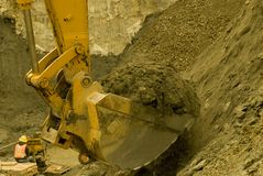 Backhoe excavating. A backhoe works while a worker rests in the background Stock Photography