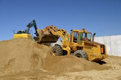 Backhoe and front end loader moving sand stock photos