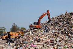Backhoe at garbage dump. Backhoe moves trash in a landfill site, pollution, Global warming royalty free stock images