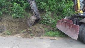 Backhoe gravende kuil aan de kant van weg stock video