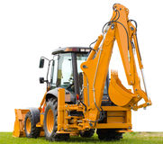 Backhoe on green grass stock photography