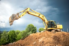 Backhoe and industrial excavator working in construction site Stock Image