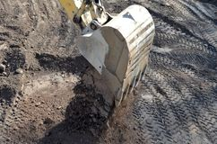 Backhoe. A large backhoe digging in the earth at a construction site stock photos