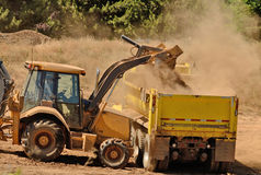 Backhoe Load. A backhoe loads duft and top soil into a 10-yard dump truck at a new commercial road development stock image
