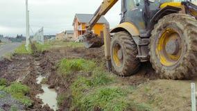 Backhoe loader digging soil. Construction site stock video footage