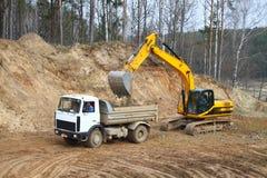 Backhoe loader loading dumper stock images