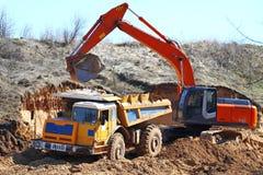 Backhoe loader loading dumper Royalty Free Stock Image