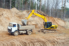 Backhoe loader loading dumper Royalty Free Stock Images