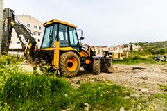 Backhoe Loader In Side Street. Backhoe loader in a side street for urban renewal projects in progress in order to create build more rugged apartments and condos Royalty Free Stock Image