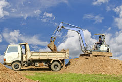 Backhoe loading a dump truck. Royalty Free Stock Image