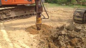 Backhoe met een boorapparaat bij een bouwwerf stock videobeelden