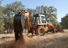 Backhoe out in the field Stock Images