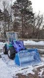 Backhoe para escavar a neve na terra Fotos de Stock