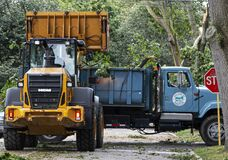 Free Backhoe Picking Up Tree Damage After Storm And Placing In Dumptruck Royalty Free Stock Photo - 172364835